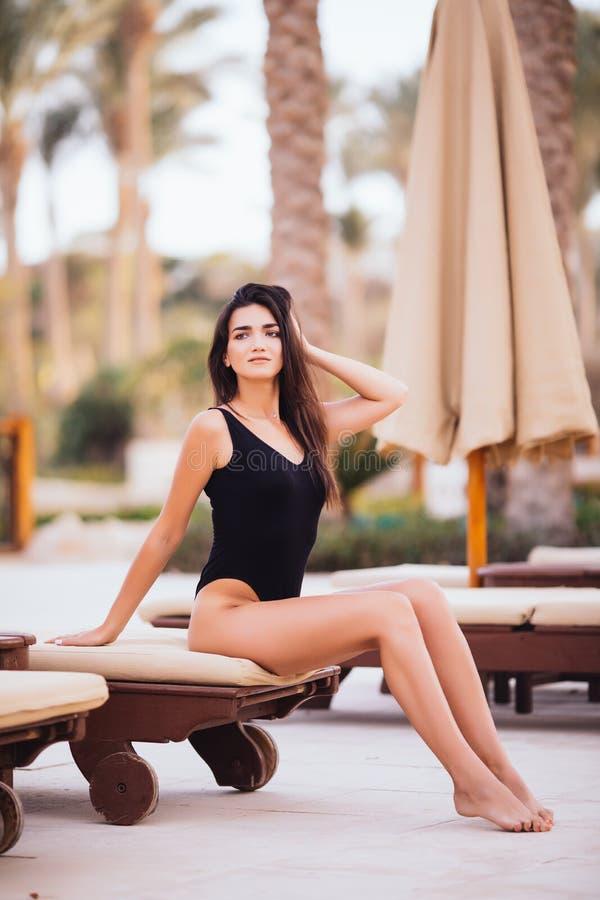 Brunette-Schönheit mit Sitz-Körper, lange Beine im eleganten weißen Bikini, moderne Sonnenbrille, hohe Absätze und Sun-Hut-Sitzen stockfoto
