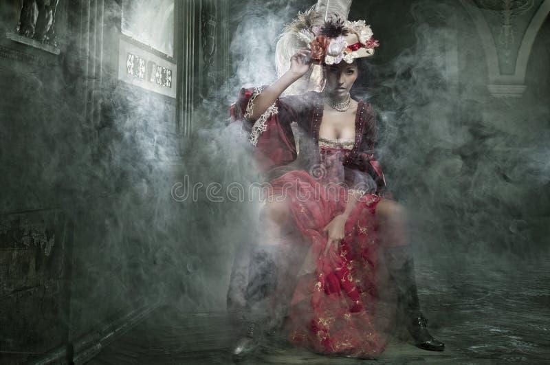 Brunette sensible s'asseyant dans une robe de cru photos stock