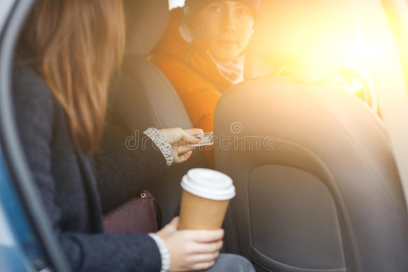 Brunette sitting in taxi sends cash for passage driver stock images