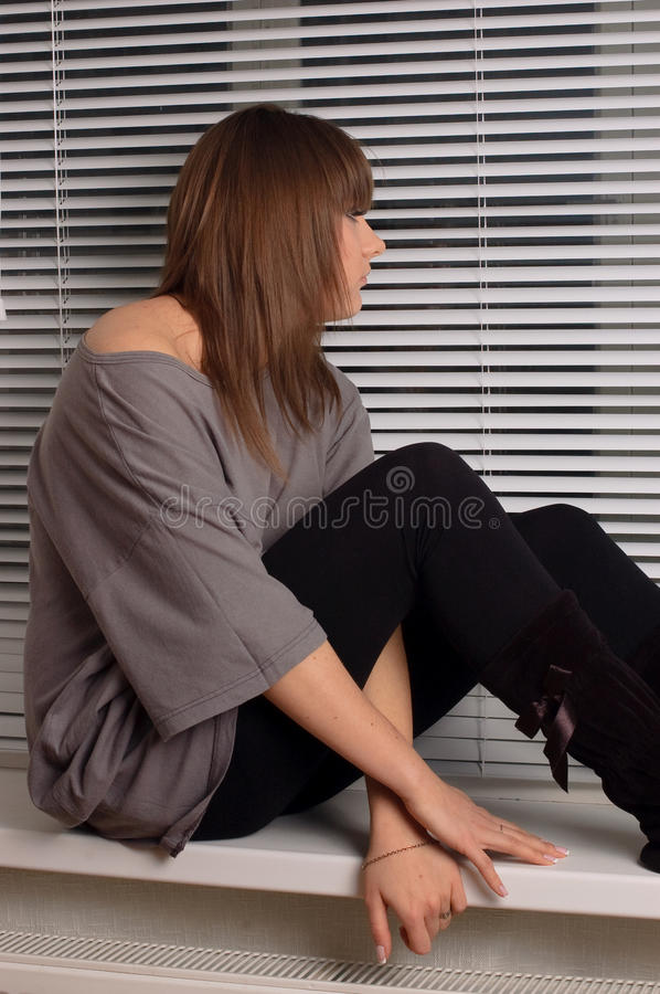 Brunette sitting on the window royalty free stock images