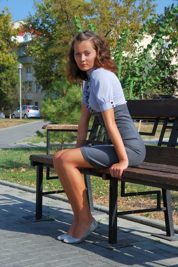 Brunette sitzt auf Bank. lizenzfreie stockbilder