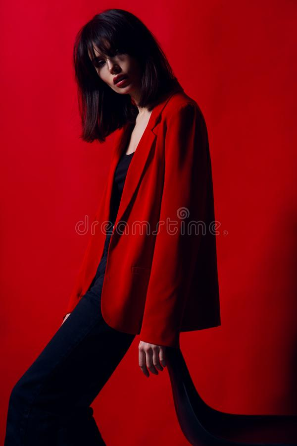 Portrait of a young woman in profile, posing in studio standing on chair in red suit,  on a red background. royalty free stock photography