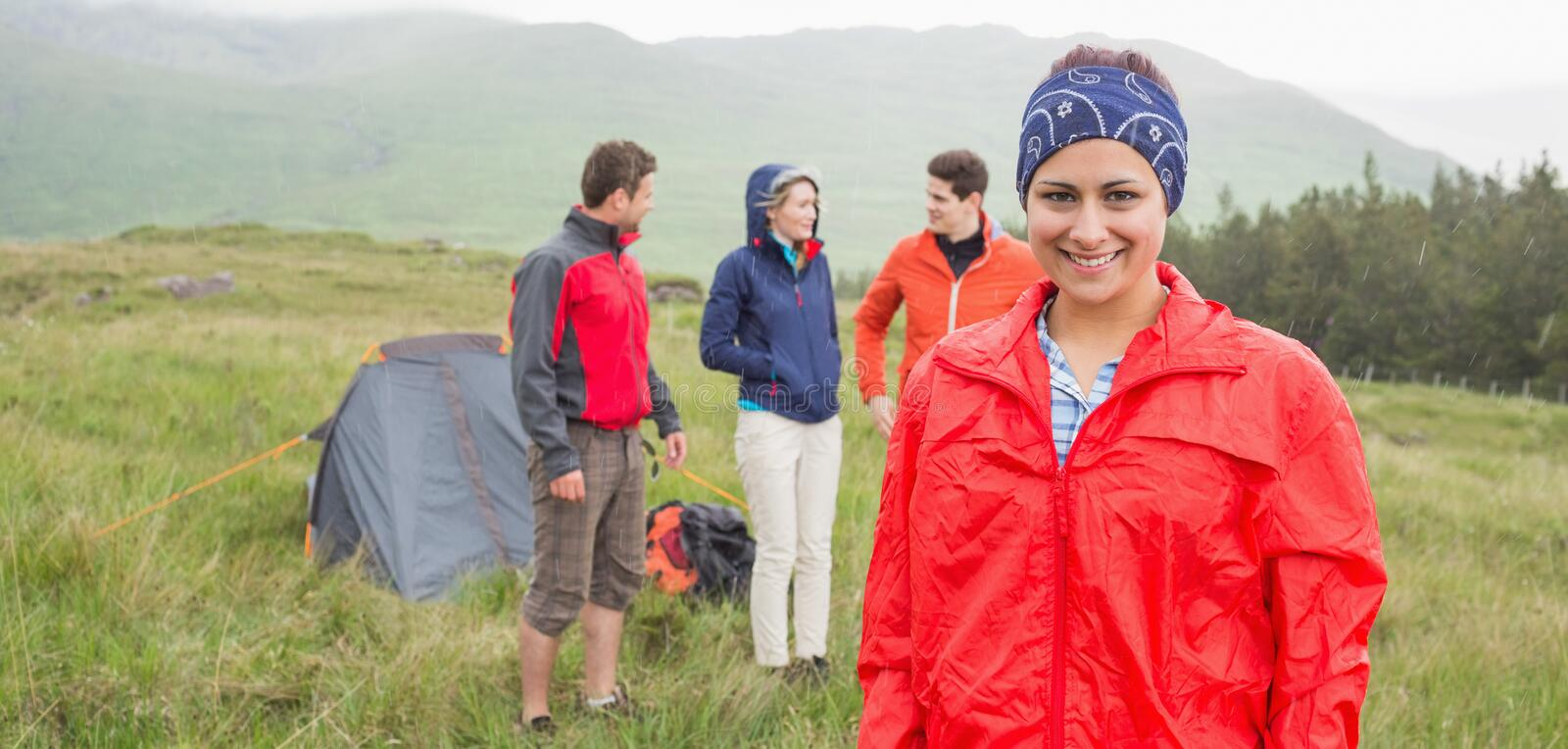 Brunette smiling at camera with friends behind her on camping trip. In the countryside royalty free stock image