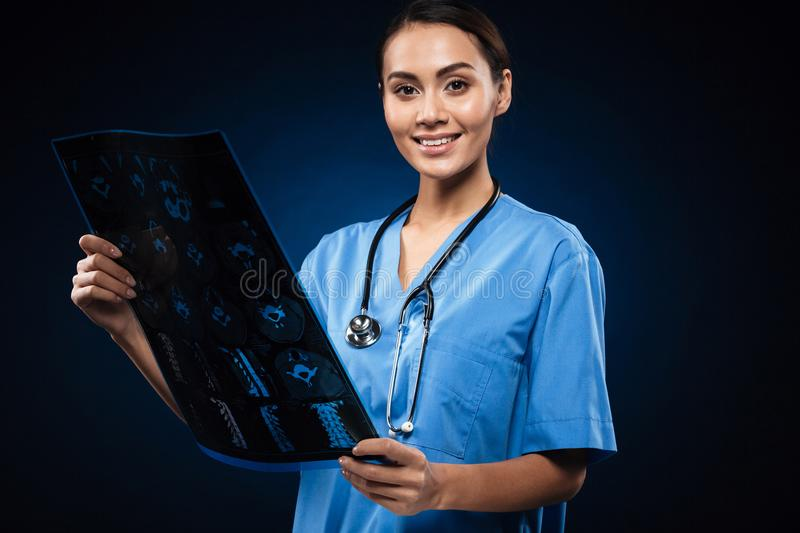 Brunette smiling doctor in uniform looking at x-ray image stock images
