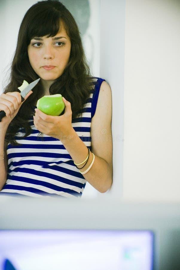 Brunette standing/eating apple