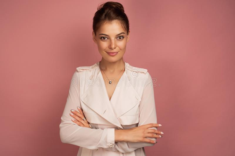 The brunette is standing on a pink background in a light trench coat with the collected hair with folded arms in front. Of her and looking at the camera stock image