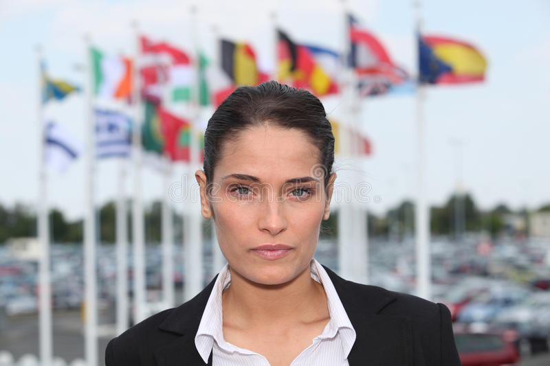 Brunette stood by flags. Brunette stood in front of flags stock image