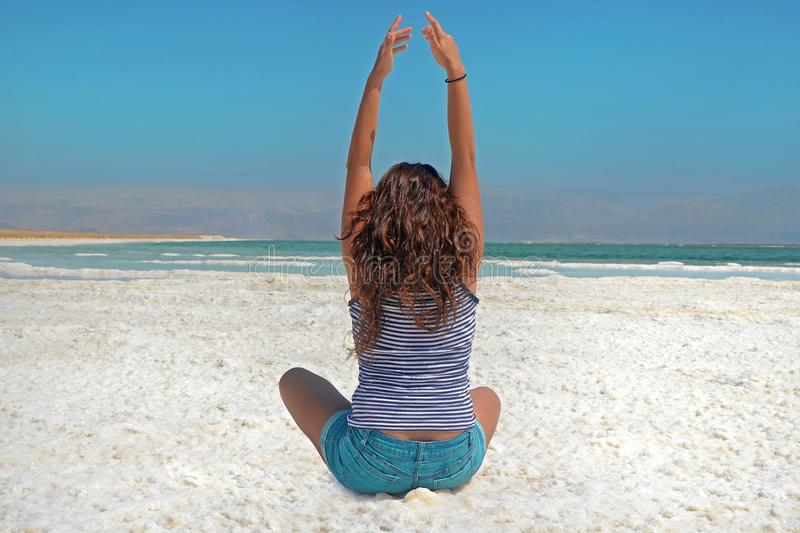 The brunette stretches her arms up, looking at the mountains of Jordan.  royalty free stock images