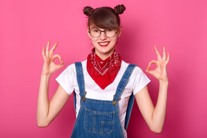 Brunette Student mit banches Lächeln, macht okayzeichen mit beiden Händen, Showzustimmung Junges Mädchen trägt weißes T-Shirt, De stockfotografie