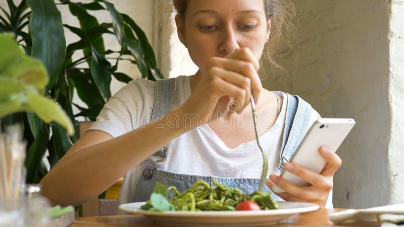 Brunette student eats green fresh salad holding smartphone stock photography