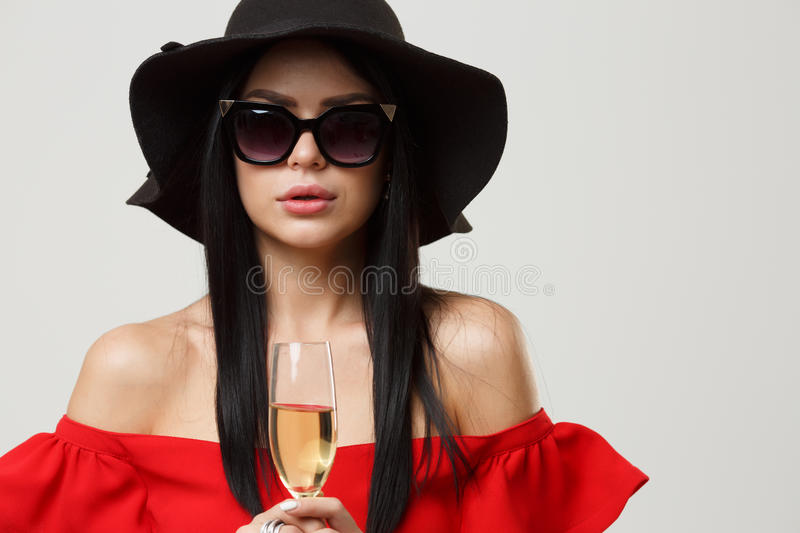Brunette in sunglasses and hat. Brunette in sunglasses and black hat in empty gray background royalty free stock photo