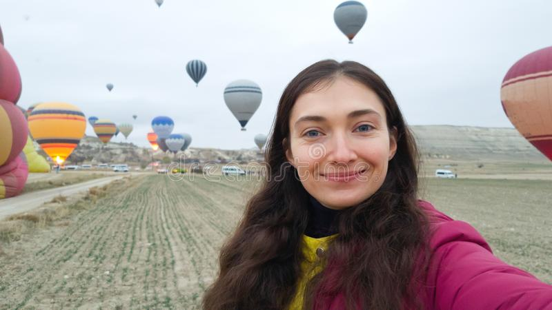 The brunette takes a selfie on the background of balloons soaring into the sky. Early morning in Cappadocia. Happy girl traveler royalty free stock photos