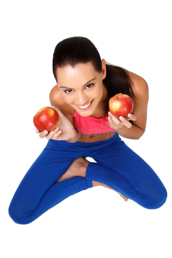 Brunette teeanger sitting on the floor with apples royalty free stock images