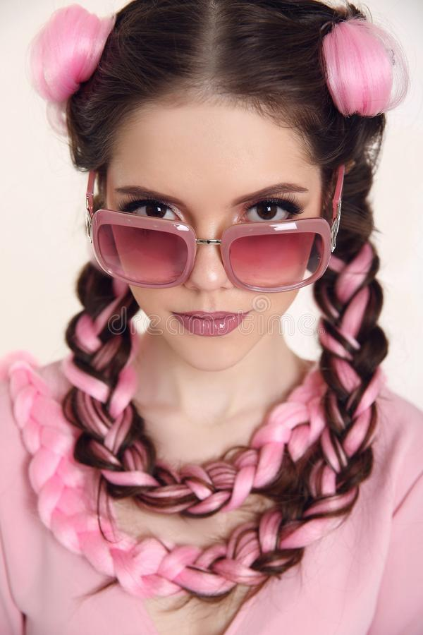 Brunette teen girl with two french braids from pink kanekalon, f stock photos