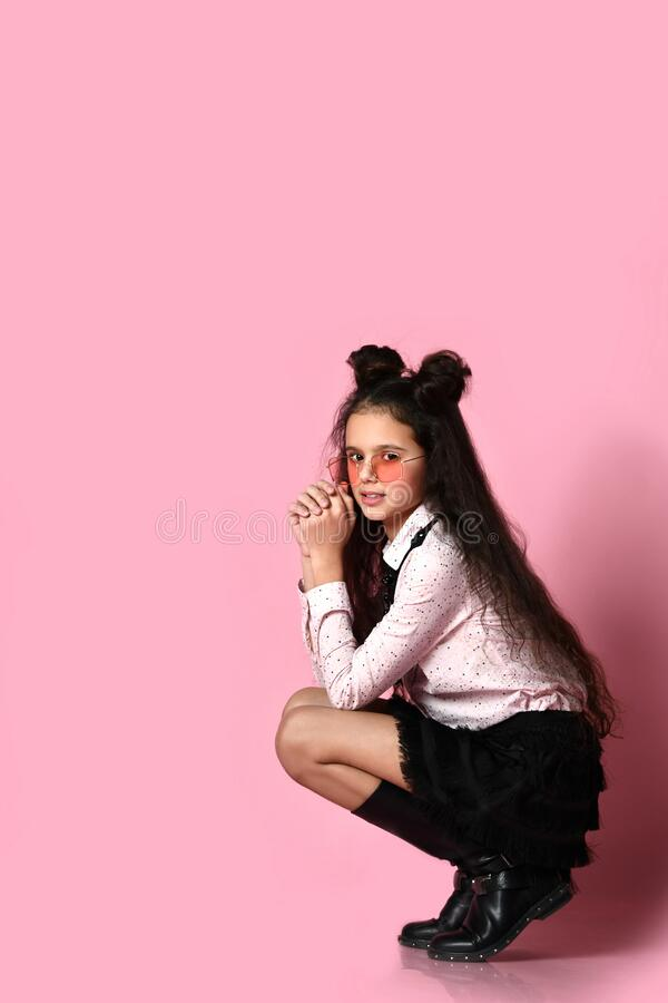 Teenage kid with long hair, in sunglasses, white blouse, black skirt and boots. She posing squatting on pink background. Close up. Brunette teenage kid with long stock images