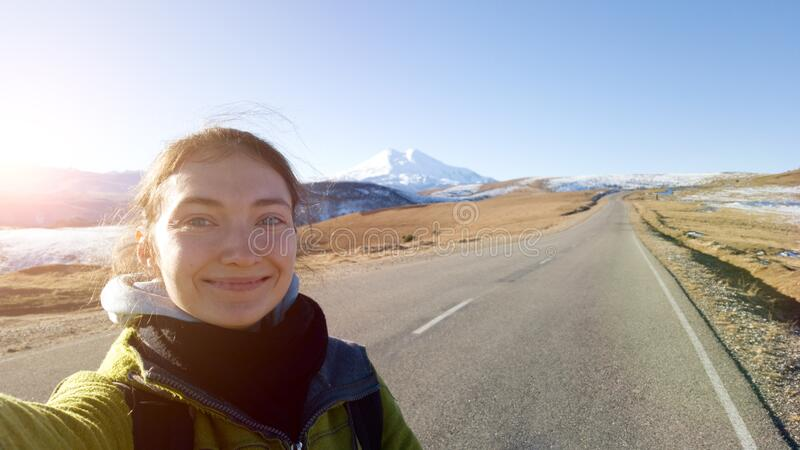 A brunette traveler girl takes a selfie on the background of an asphalt road in the direction of mount Elbrus. Hitchhiking. royalty free stock image