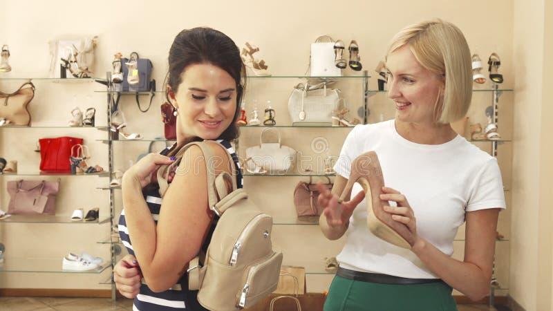 Women choosing bag and shoes in shoe shop stock image