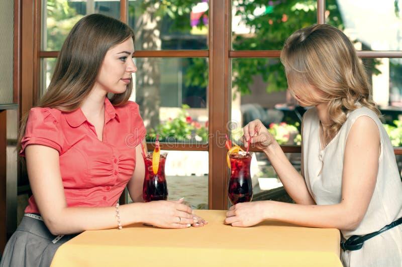 Brunette und Blondine trinken Fruchtgetränk lizenzfreie stockfotos