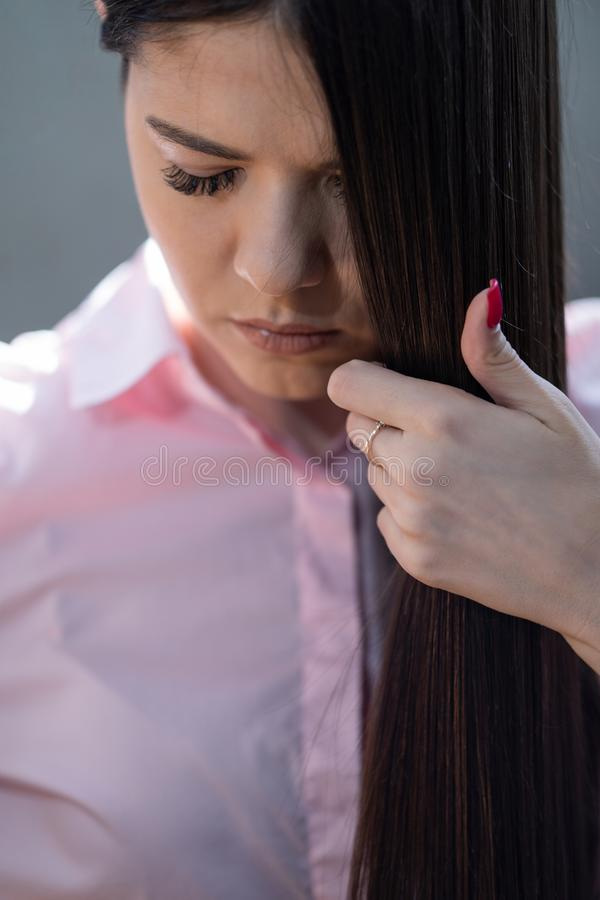 Brunette with very beautiful hair in a pink shirt royalty free stock photo
