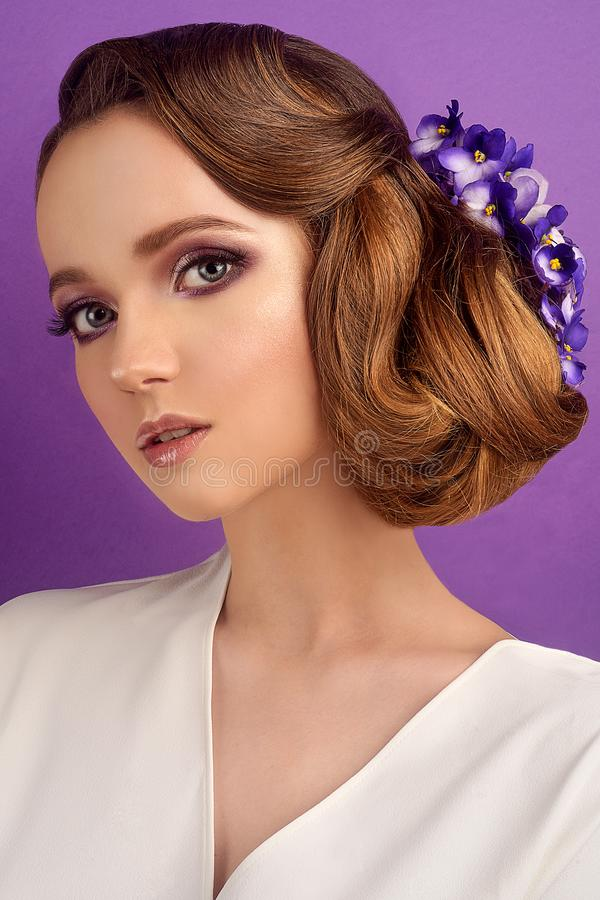 Brunette on a violet background. Girl with professional make-up and hairstyle. Beauty salon. Girl with blue flowers in her hair. stock photography