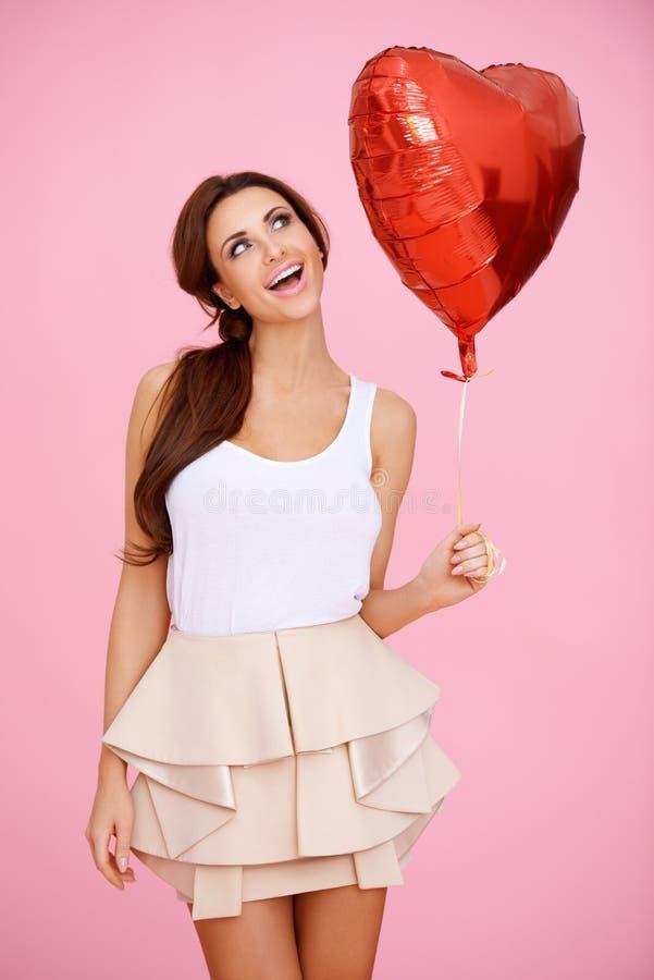 Brunette Vivacious com um balão vermelho do coração fotos de stock