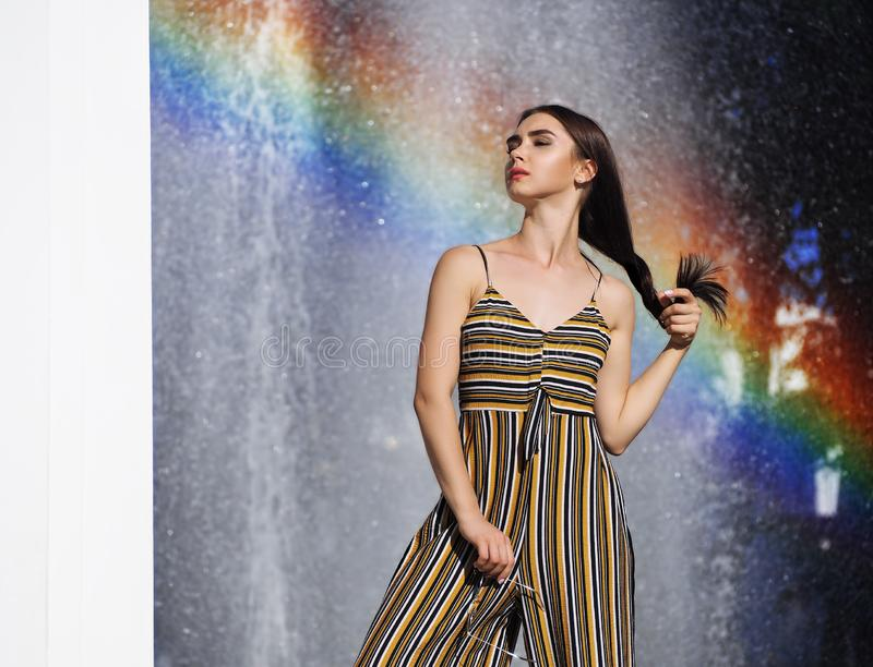Brunette vorbildliche Stellung des M?dchens und nahe aufwerfen mit Regenbogen lizenzfreie stockfotos