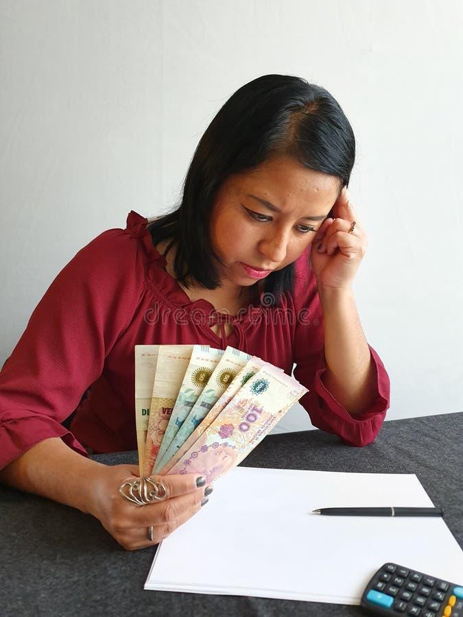 brunette vrouw analyseert economische begroting en houdt Argentijns geld in handen stock foto