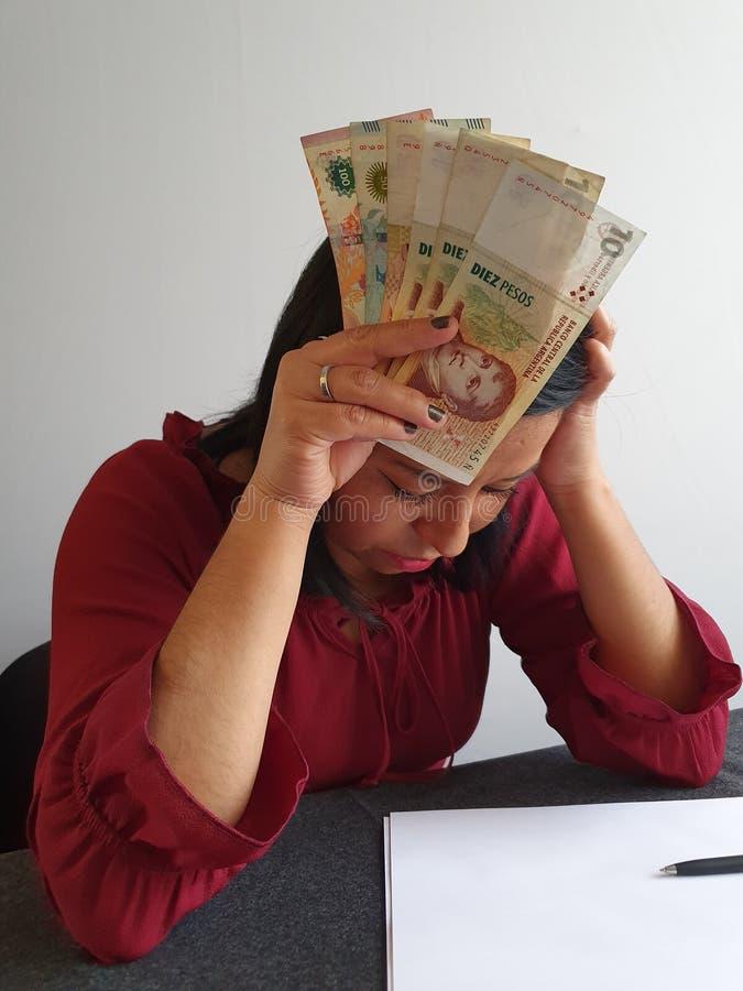 brunette vrouw die wanhoop uitstraalt en Argentijns geld pakt stock foto's