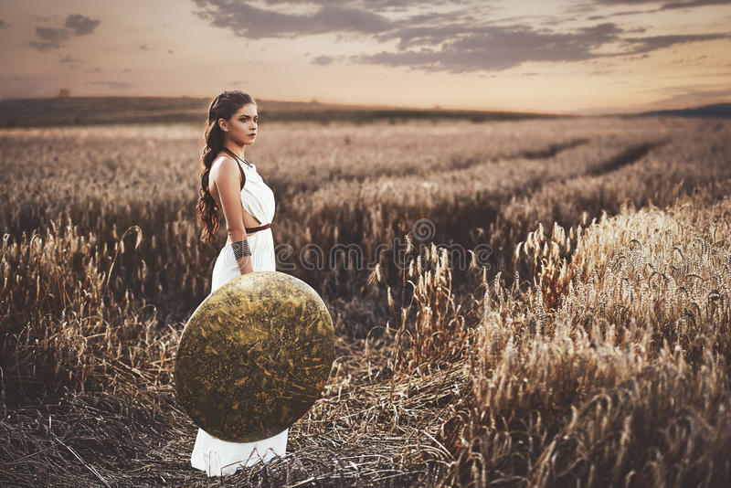 Brunette wearing in dress like greece style holding shield. stock images