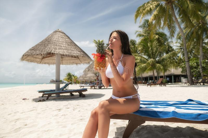 A brunette in a white bathing suit sits on a lounger and drinks a Pina Colada cocktail in a pineapple stock photo