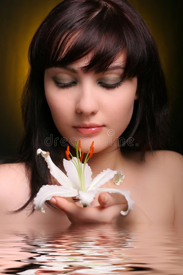 Brunette with white lily flowers in water. 2 stock photo