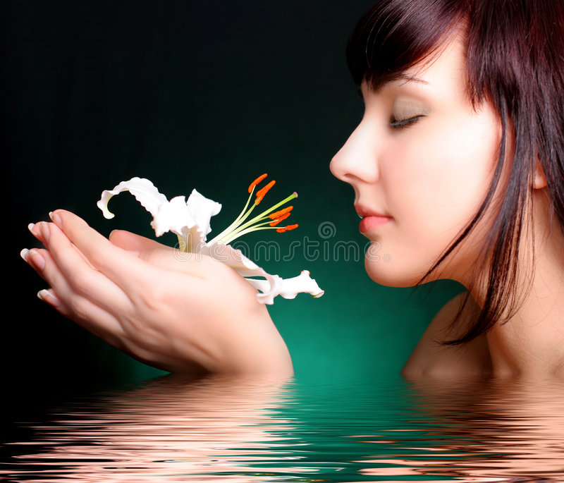 Brunette with white lily flowers in water royalty free stock photography