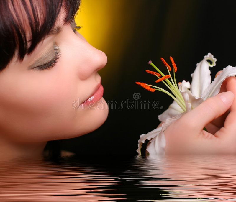 Brunette with white lily flowers in water stock image