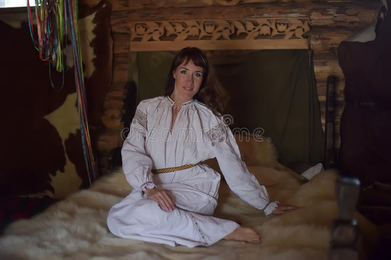 Brunette in white linen old-fashioned shirt with embroidery sits on a medieval bed stock images
