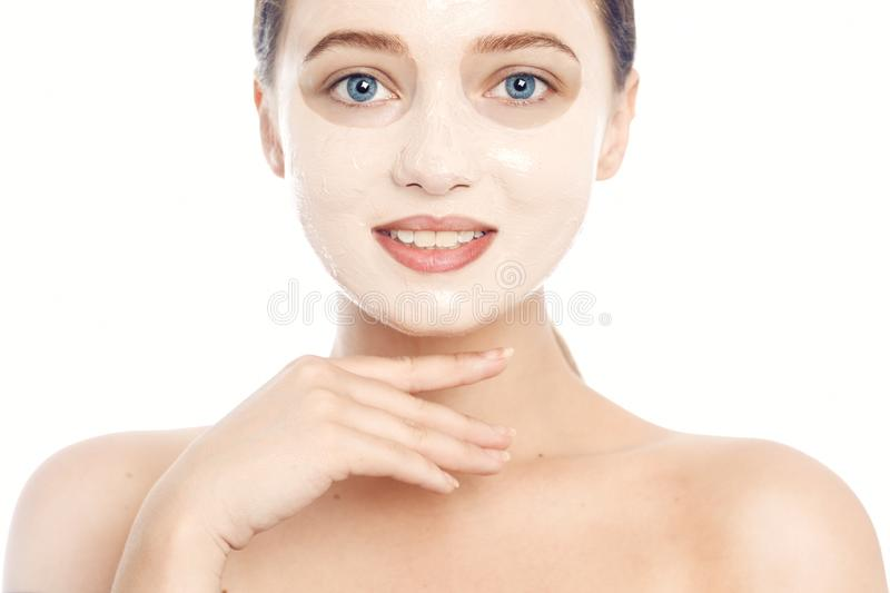 Brunette in a white mask for the face. Beautiful photo of a girl with perfect skin. A young girl cares for herself. Studio photo stock image