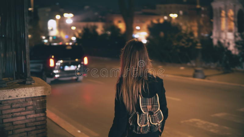 Brunette woman with backpack walking late at night. Attractive girl goes through the city centre near road in evening. royalty free stock images