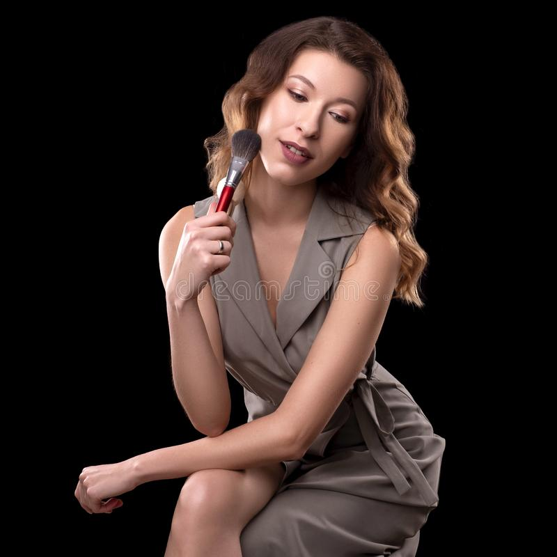 Brunette woman beautician on a neutral background. She holds beauty instruments in her hands.  stock photo
