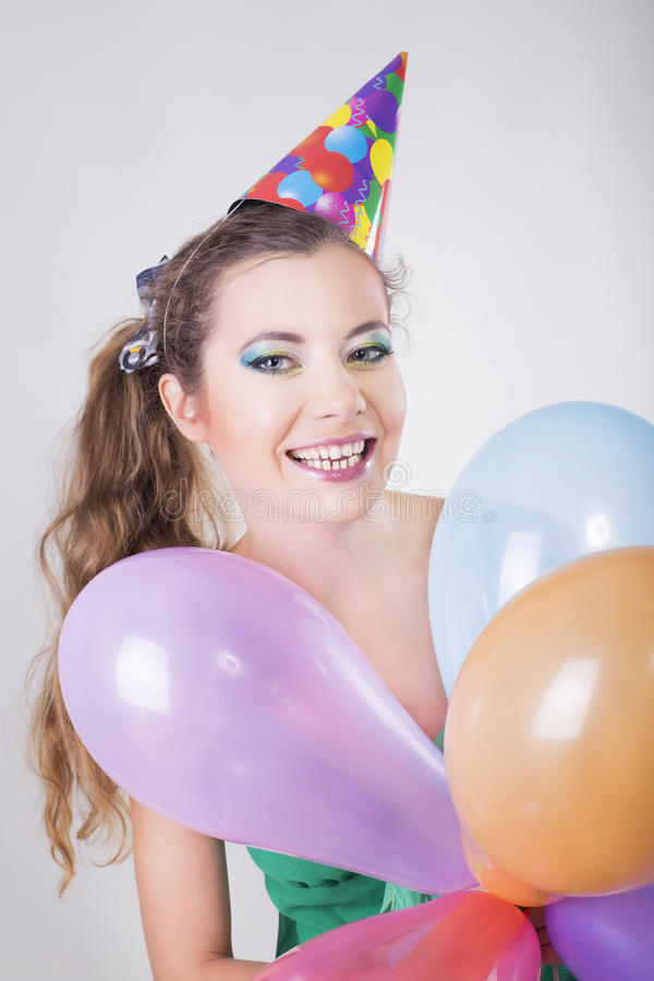 Brunette Woman in a Birthday Cap Holding Balloons and Smile. Happily stock images
