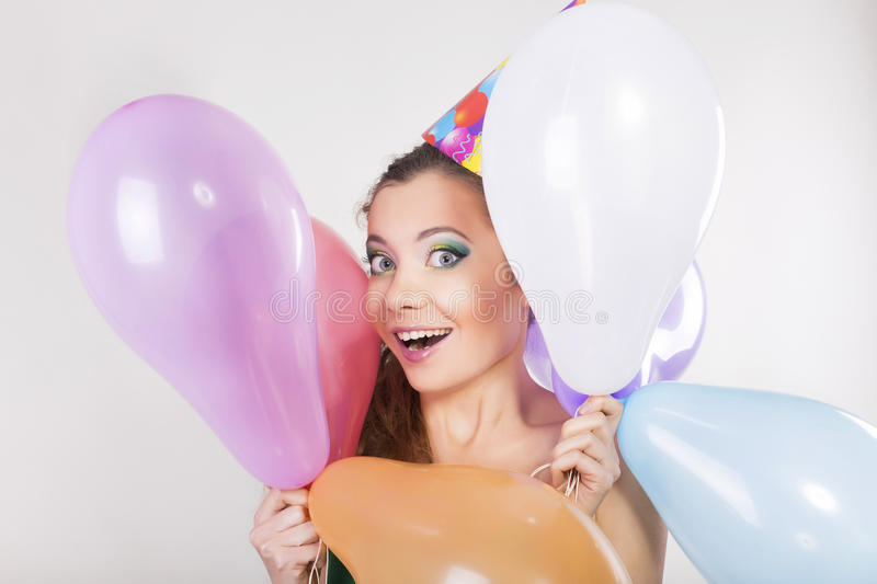 Brunette Woman in a Birthday Cap Holding Balloons and Smile. Happily royalty free stock image