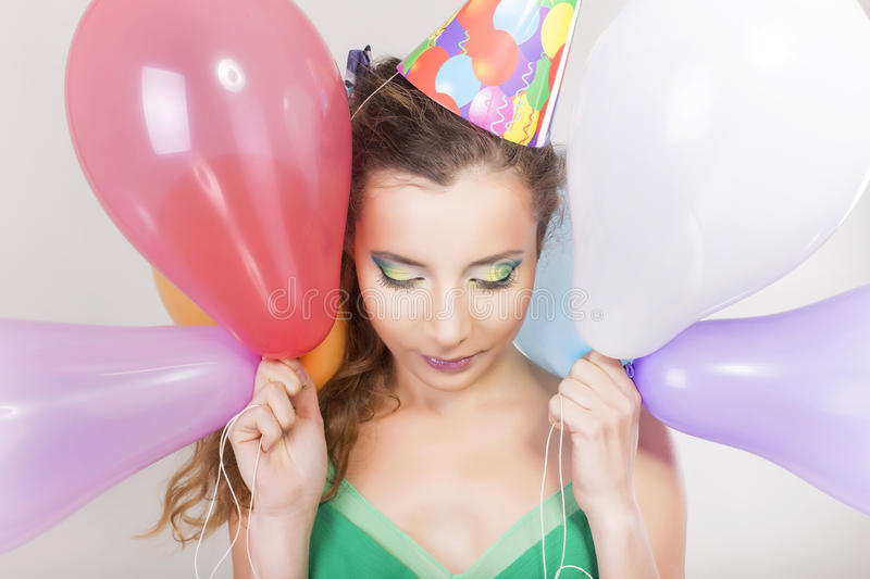Brunette Woman in a Birthday Cap Holding Balloons and Smile. Happily stock photo