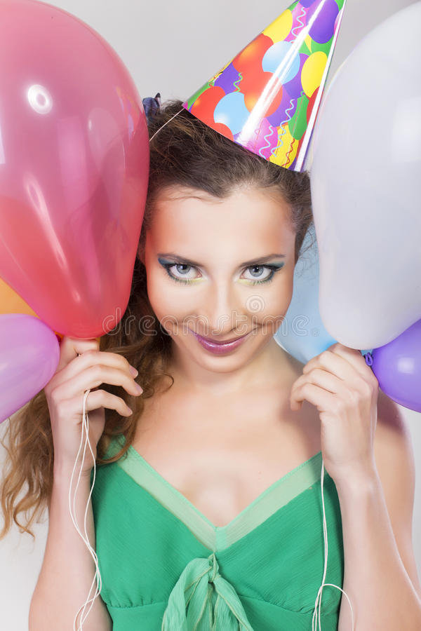 Brunette Woman in a Birthday Cap Holding Balloons and Smile. Happily stock image