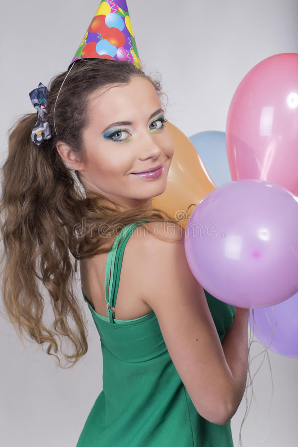 Brunette Woman in a Birthday Cap Holding Balloons and Smile. Happily stock photos