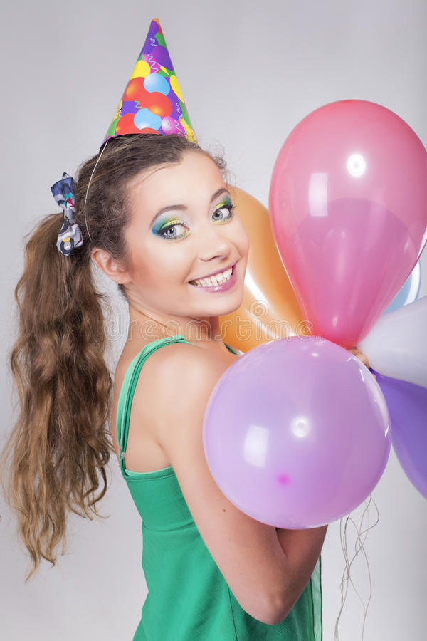 Brunette Woman in a Birthday Cap Holding Balloons and Smile. Happily royalty free stock photos