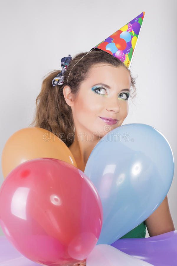 Brunette Woman in a Birthday Cap Holding Balloons and Smile. Happily royalty free stock images