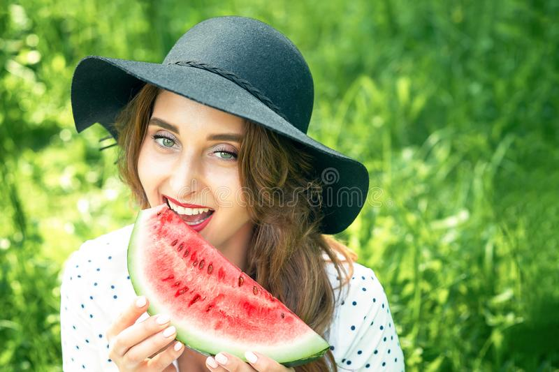 Brunette woman in black hat is eating fresh watermelon slice on the background of green nature stock photography