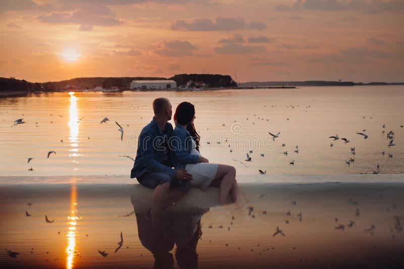 Brunette woman and blonde man looking at birds and relaxing. Romantic evening of family near picturesque bay. Side view of couple of young people in casual stock photo