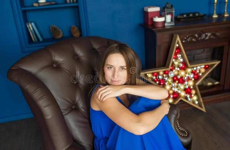 Brunette woman in blue dress looks at camera sitting on armchair in blue room. stock photos