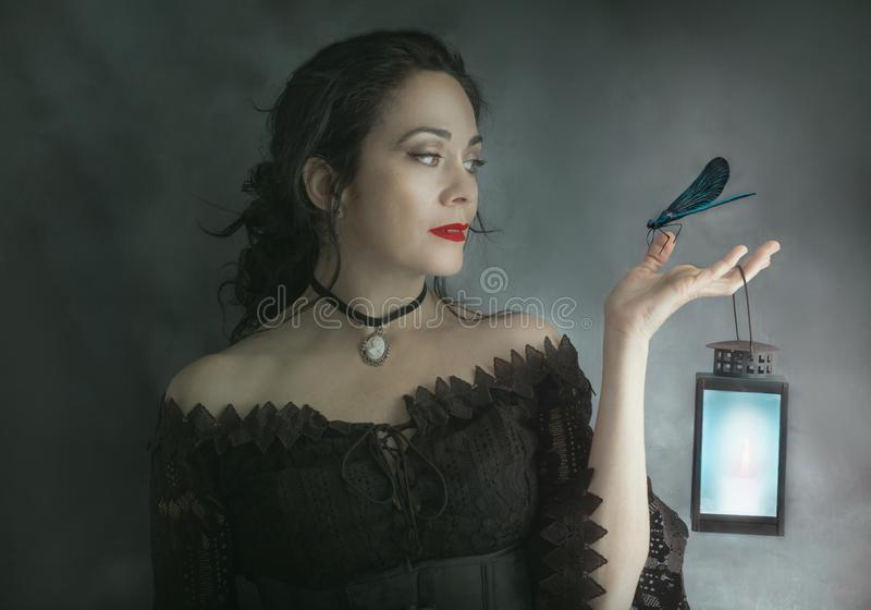 Brunette woman with blue light candle and dragonfly in her hand. Fantasy photography stock images