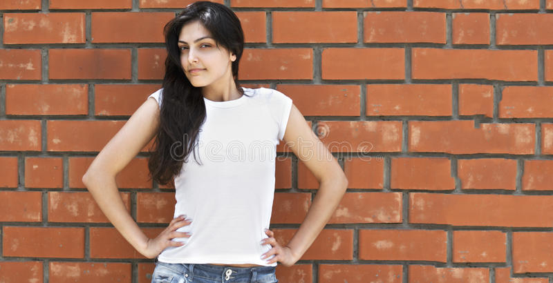 Brunette woman at brick wall royalty free stock image