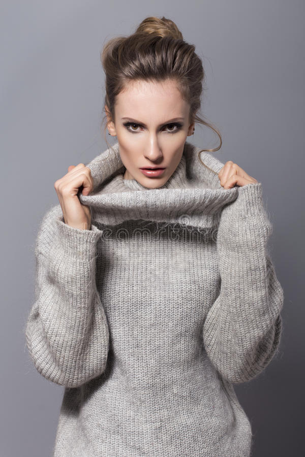 Brunette woman with bun hairstyle and neutral make up posing in. Grey sweater on a grey background stock photos